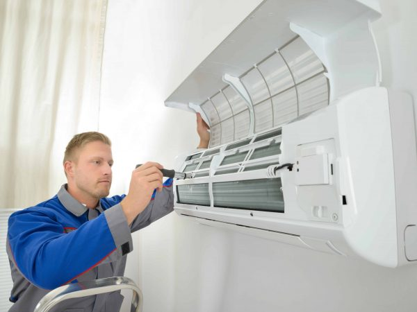 Young Man Repairing Air Conditioner Standing On Stepladder