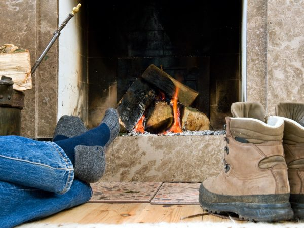 6553527 – hiker warming up and relaxing by a small fireplace